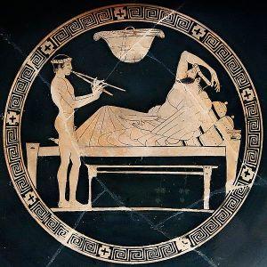Un joven desnudo toca el aulos para el comensal de un banquete. Copa roja ática, pintor de Eveón, 460-450 a. C.